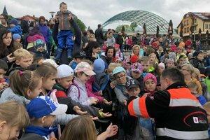 Potápač z Oravského záchranného systému rozdáva deťom sladkosti.