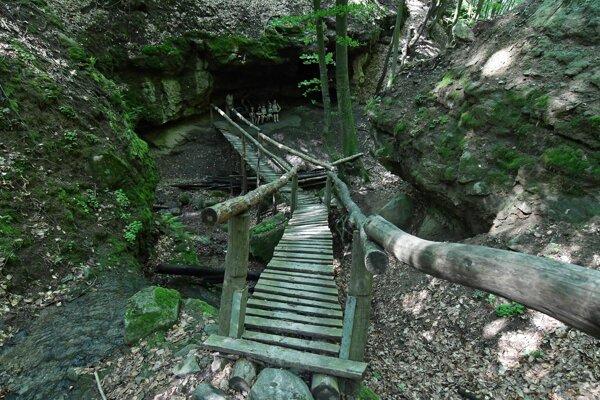 Krížom cez roklinu je položený drevený mostík, vedúci pod skalný previs.