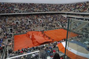 Zriadenci zakrývajú dvorec pre dážď počas semifinálového zápasu dvojhry mužov Dominic Thiem - Novak Djokovič na Roland Garros 2019.