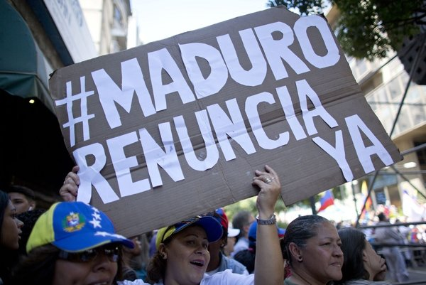 Žena drží nápis, ktorým vyzýva venezuelského prezidenta Madura na odstúpenie.