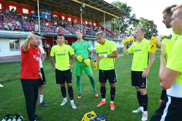 Tréner Slavče Vojneski rozdáva pokyny počas polčasovej prestávky.