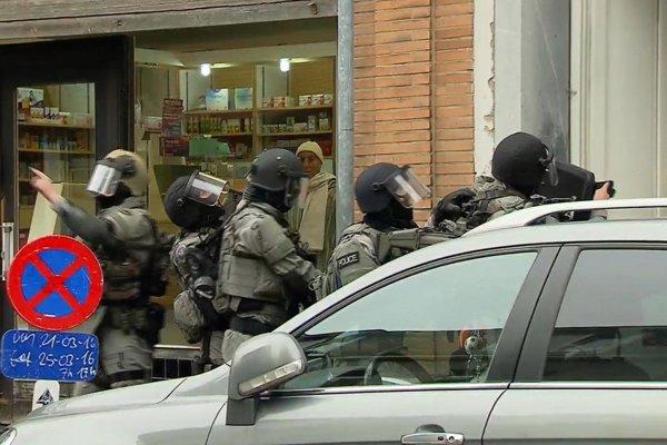 Policajti vnikajú do bruselského bytu vo štvrti Molenbeek.
