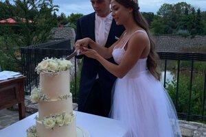 Mladomanželia počas krájania svadobnej torty.
