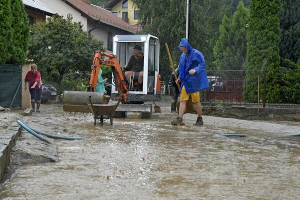 Odpratávanie vody a bahna zo zaplavenej ulice v obci Ratnovce.