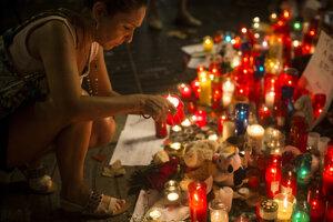 Žena zapaľuje sviečku na pamiatku obetí teroristického útoku v centrálnej Barcelone 20. augusta 2017.