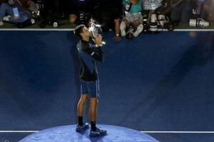 Novak Djokovič bozkáva trofej pre šampióna US Open 2018.