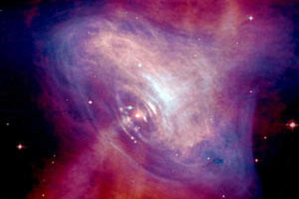 Zložený, opticko/röntgenový obrázok pulzaru Krabia hmlovina, ktorý ukazuje okolité plyny v hmlovine, ktoré sú rozvírené pôsobením magnetického poľa a žiarenia pulzaru.
