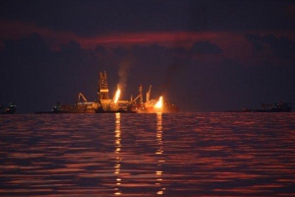 Apokalyptický obrázok plošiny Deepwater Horizon po havárii v júni 2010 uprostred oceánu pokrytého ropou.