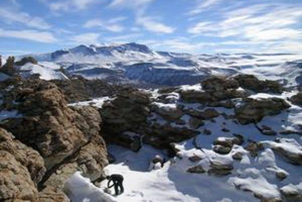 Americký geológ odoberá vzorky pri špici antarktického horského vrcholu.