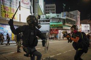 Novinár natáča policajta počas zásahu proti demonštrantom.