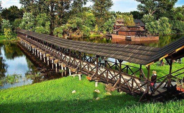 K mlynu vedie údajne najdlhší zastrešený drevený riečny most vEurópe.