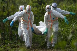Zdravotníci v ochranných oblekoch odnášajú mŕtvolu obete eboly v Tanzánii.