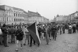 Zhromaždenie študentov 21.11.1989, v čiernom kabáte za zástavou M. Števík.
