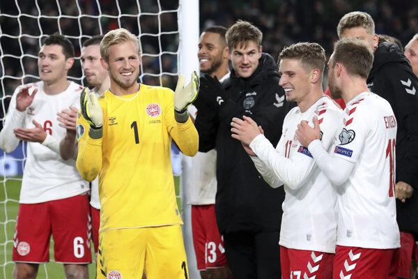 Dánsky brankár Kasper Schmeichel (druhý zľava) oslavuje so spoluhráčmi na ihrisku po postupe na ME na konci zápasu D-skupiny Írsko - Dánsko.