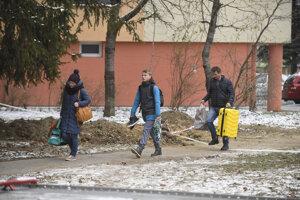Evakuovaní ľudia si odnášajú veci z vedľajších bytových domov pri zhorenej bytovke.