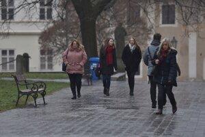 Ľudia kráčajú po posypanom chodníku počas silnej námrazy v Trnave.