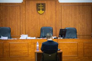 Peter Tóth sedí na mieste pre svedkov počas prestávky.