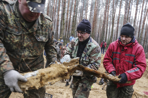 Traja muži nesú trosky bombardéra z druhej svetovej vojny používaného sovietskymi vzdušnými silami, ktorý bol zostrelený pred 75 rokmi, objavili historici v lese neďaleko poľského mesta Bieruň v nedeľu 19. januára 2020.
