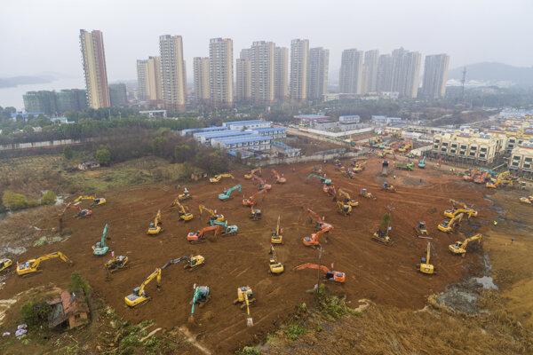 Ťažké stavebné stroje pracujú na stavebnom pozemku budúcej nemocnice v meste Wu-chan v strednej Číne.
