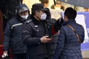 Policajt meria teplotu turistovi v Nankingu.