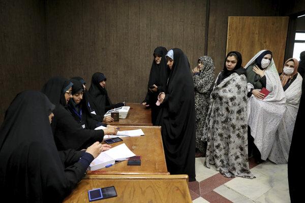 Iránske ženy čakajú v rade vo volebnej miestnosti.