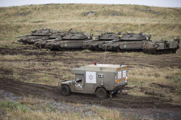 Izraelská vojenská sanitka prechádza okolo tankov na Izraelom kontrolovanom území Golanských výšin neďaleko hranice so Sýriou.
