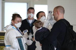 Hygienici rezortu dopravy merajú teplotu cestujúcemu v príletovej hale na Letisku M. R. Štefánika.