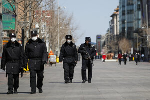 Hliadky čínskej polície kráčajú po ulici v Pekingu