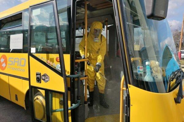 Dobrovoľníci z jednotky civilnej ochrany v Chrenovci-Brusne dezinfikujú autobusy SAD Prievidza.