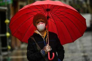 Žena s rúškom a rukavicami pod dáždnikom na ulici v daždi v španielskej Pamplone.