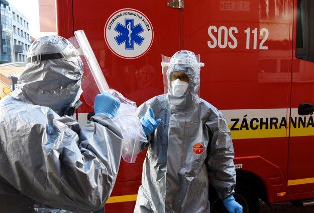 Hasiči s odobratými vzorkami od pacienta podozrivého na ochorenie na koronavírus v jednej z bratislavských štvrtí.