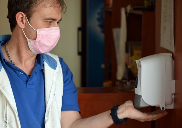 Čašník s ochranným rúškom si dezinfikuje ruky počas provizórneho výdaja balených obedov v súvislosti s opatreniami proti šíreniu koronavírusu v reštaurácii v Trebišove.