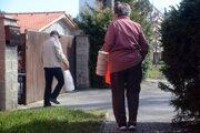Dôchodcovia prichádzajú k miestu výdaja obedov dotovaných mestom určených seniorom na Sliači.