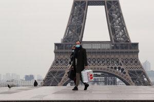 Dvojica s ochrannými rúškami kráča cez prázdne námestie Trocadéro pred Eiffelovou vežou v Paríži.