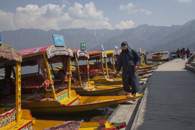 Zamestnanec v ochrannom odeve dezinfikuje šikary, tradičné drevené člny, ako prevenciu pred šírením koronavírusu a ochorením COVID-19 v Šrínagare, indickej časti Kašmíru.