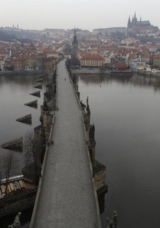 Žena kráča po opustenom Karlovom moste v Prahe.