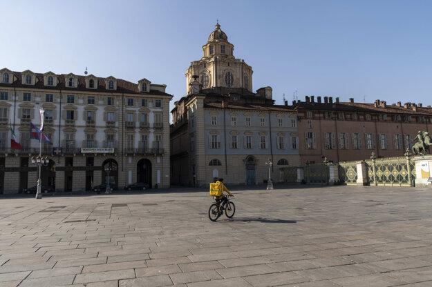 Kuriér rozvážajúci jedlo ide na bicykli cez hlavné turínske námestie Piazza Castello, ktoré sa nachádza priamo v centre Turína v Taliansku.