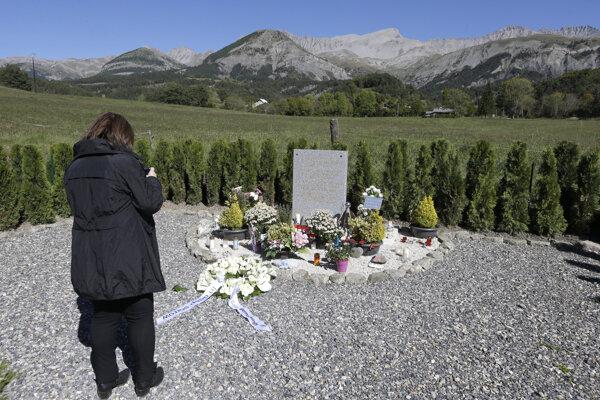 Na archívnej snímke z roku 2015 žena stojí pri pamätnom kameni v Le Vernet.