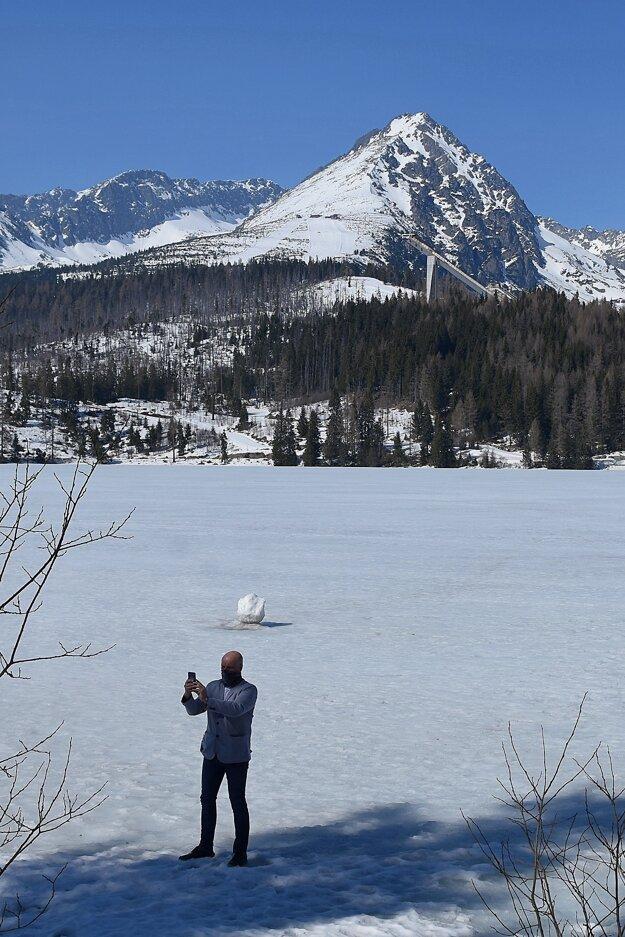 Muž sa fotí mobilom na zamrznutom jazere na Štrbskom Plese vo Vysokých Tatrách.