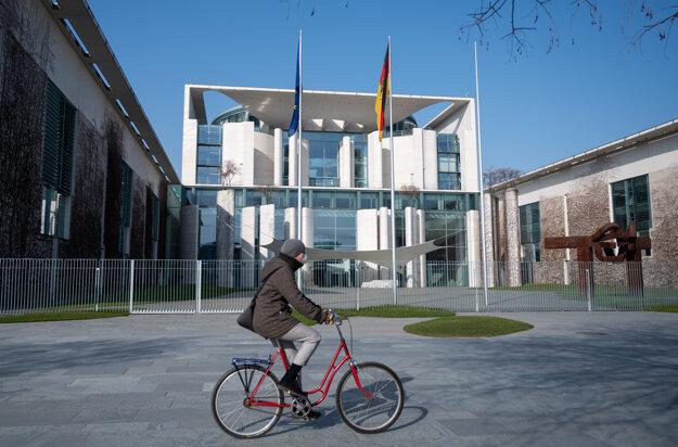 Cyklistka prechádza okolo spolkového úradu v Berlíne.