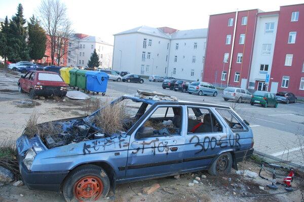 Vraky dvoch osobných áut na parkovisku v bývalých kasárňach