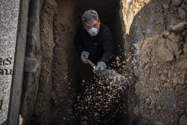 Muž pripravuje hrob na pohreb obete ochorenia Covid-19 na cintoríne v Madride.