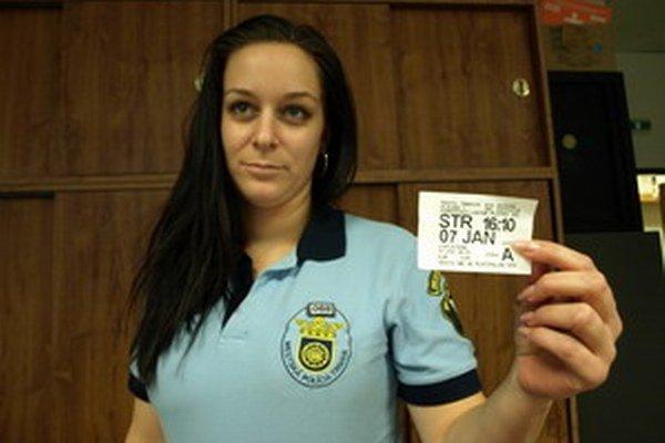 Mestská policajtka ukazuje falošný parkovací lístok, ktorý objavili na Pekárskej ulici.