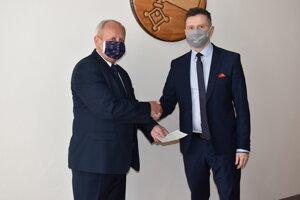 Ján Voloch (vľavo) si od primátora Miloša Merička prevzal osvedčenie.