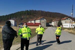Pracovníci MOPS hliadkujú pred vstupom na sídlisko.