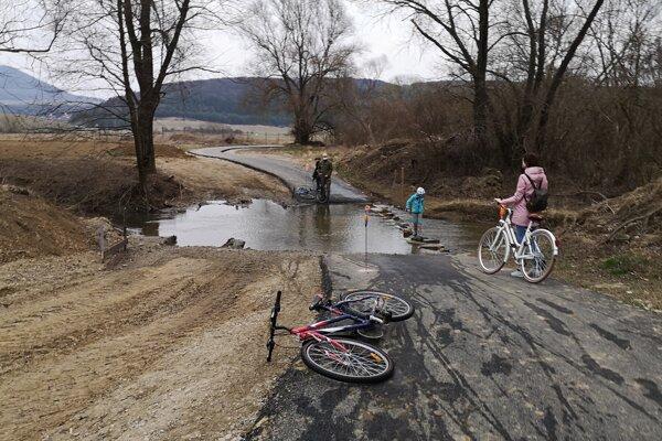 Niektorí cyklisti zosadajú z bicyklov, iní cez potok prefrčia na ňom.