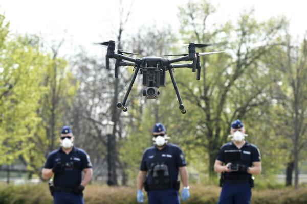Policajti s ochrannými rúškami na tvári používajú dron na kontrolu ľudí počas obmedzenia pohybu.