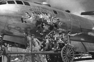 """Posádka amerického bombardéra """"Waddy's Wagon"""" pred prvou japonskou misiou na Saipane v novembri 1944 napodňuje vlastné karikatúry na nose lietadla."""