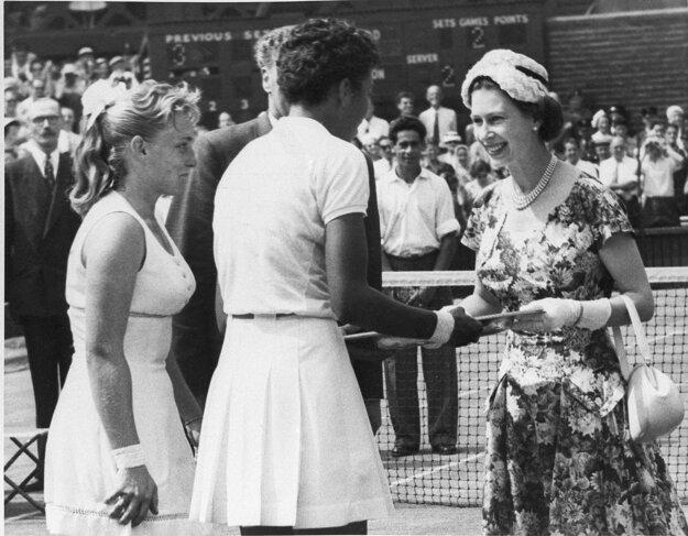 Na snímke zo 6. júla 1957 britská kráľovná Alžbeta II. odovzdáva trofej Althey Gibsonovej, ktorá zvíťazila nad Darlene Hardovou (vľavo) na grandslamovom turnaji vo Wimbledone.