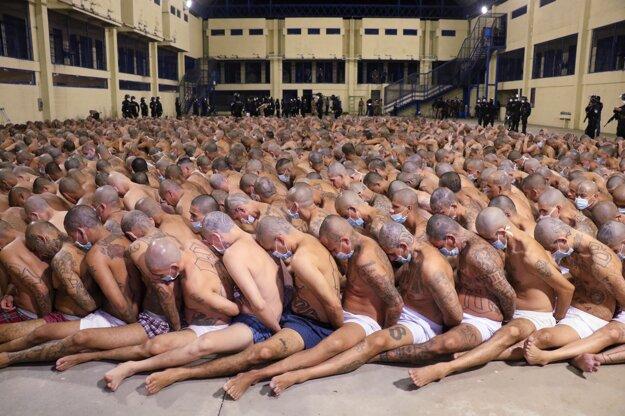 Koronavírus vo svete: Dozorcovia s rúškami strážia väzňov sediacich na zemi v rúškach vo väznici v Salvádore.
